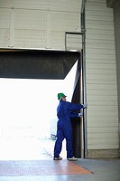 Man standing handling a roller shutter
