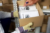 Hand browsing through documents in a box