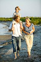 Family walks on the beach, the boy is sitting on his fathers shoulders