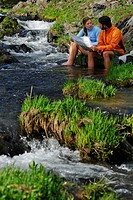 Pair of hikers checking a map while soaking feet in stream