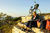 Woman with bike is reading a magazine