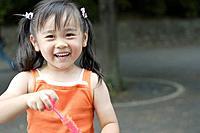 Smiling girl holding bubble gun