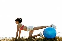 A young woman exercising under sunlight as she rests her leg on the ball with her hands touching the ground