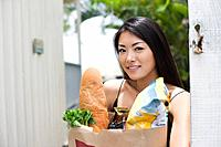 A young woman holding paper bag with groceries