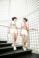 Two young women walk down the stairs after their exercise