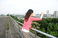 A young woman looks down and waves her hand as she stands against the railing