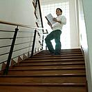 Low angle view of a businessman standing on a staircase with a file in his hand