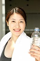 A woman holding bottle of water smiles at the camera