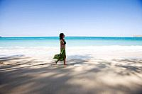 Side view of a young woman walking on beach