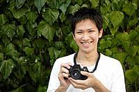 Portrait of a young man holding camera