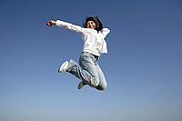 Low angle view of a smiling young woman jumping in air