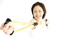 A young woman smiles as she uses the stretching rope for an exercise
