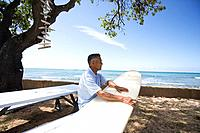 Mature man sitting on bench with surfboard