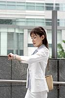 A woman looking at her watch as she is on her way