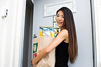 A young woman holding paper bag