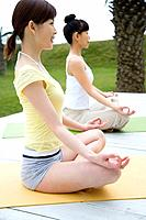 Young women sitting cross-legged, doing yoga exercise, side view (thumbnail)