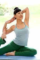 Young woman doing yoga exercise, stretching, side view