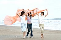 Three young women at beach, holding a shawl in the air, side view