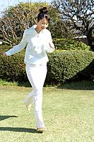 Woman running in garden, smiling, front view