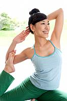 Young woman doing yoga exercise, stretching, side view, close up