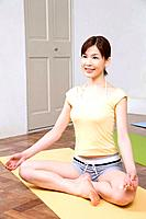 Young woman sitting cross_legged, doing yoga exercise, side view