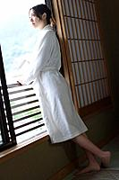 Woman in bathrobe looking outside from the window, side view, Japan