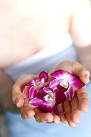 Woman in hot tub holding flower heads, high angle view, close up, Japan