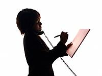 Bsinesswoman holding handset by shoulder and writing down on paper, Side View, Silhouette