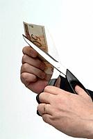 man cutting a money bill