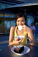 Young Lady Sitting Outdoor Cafe, Holding Cup, Smiling
