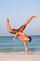 Asia, Thailand, Young man practicing capoeira on beach