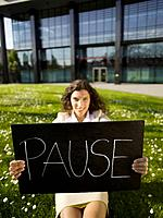 Germany, Baden_Württemberg, Stuttgart, Business woman taking a break, holding sign