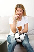 Young woman with German colours on her face eating salted sticks