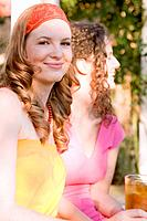 Two young women with iced tea at a garden party