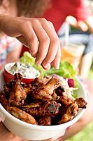 Hand reaching for grilled chicken wings