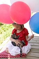 Small girl holding cat and balloons 4th of July, USA