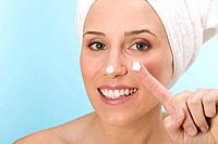 Woman with a blob of face cream on nose and finger
