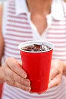 Woman holding beaker of cola with ice cubes