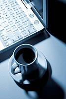 a coffee cup near a laptop computer