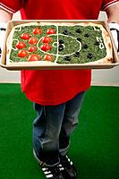 Female footballer holding spinach pizza with tomatoes & olives