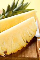 Wedges of pineapple on chopping board