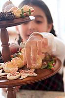 Girl reaching for Christmas biscuit on tiered stand