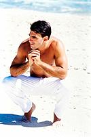 a young man barefoot on the beach sands