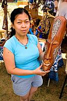 Asian woman holding decorative face sculpture for sale at her booth  Dragon Festival Lake Phalen Park St Paul Minnesota USA
