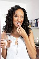 Woman taking medication smiling indoors portrait