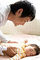 Father laying baby on bed, smiling