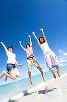 Three young people jumping on beach, smiling, Saipan