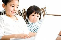 Girl and boy sitting together, looking at laptop computer