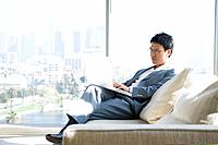 Businessman using laptop, sitting on couch