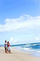 Senior couple walking on beach, hand in hand, copy space